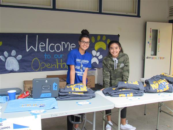 Price students man a booth at open house